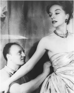 Pierre Balmain adjusting one of his evening dresses. © CORBIS.