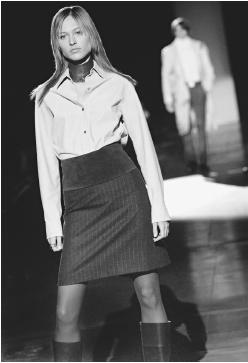 Kenneth Cole, fall 2001 collection: napa leather shirt, pinstripe skirt, wide suede belt, and wrap choke collar. © AP/Wide World Photos.