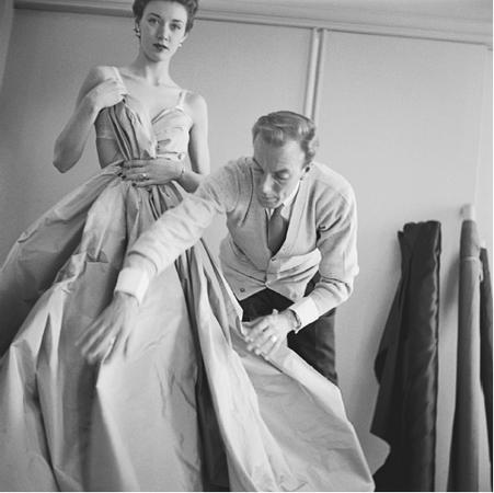 Jacques Fath adjusting one of his ball gowns, 1951. © Genevieve Naylor/CORBIS.