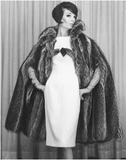 Anne Fogarty, fall 1964 collection: wool dress with a satin pull-through bow under a raccoon fur cape coat. © AP/Wide World Photos.