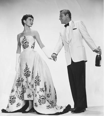 Audrey Hepburn, with William Holden, in a publicity still from the film Sabrina (1954) wearing a gown designed by Hubert de Givenchy. © Bettmann/CORBIS.