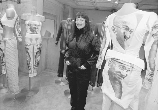 Norma Kamali standing in her Manhatten showroom with part of her spring 1997 line, featuring silkscreens of Mahatma Ghandi. © AP/Wide World Photos.