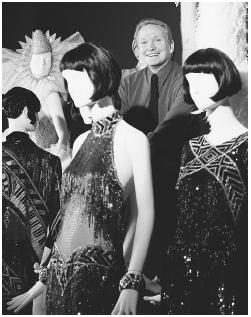 "Bob Mackie posing with some of his designs at the ""Unmistakably Mackie"" retrospective at the Fashion Institute of Technology in New York, 1999. © AP/Wide World Photos."